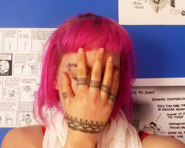 Tatouage inuit sur main, cheveux roses sur la tête