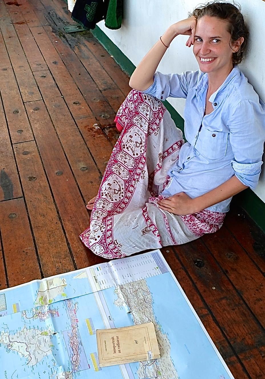 Anne Becel qui adore voyager léger assise devant une carte
