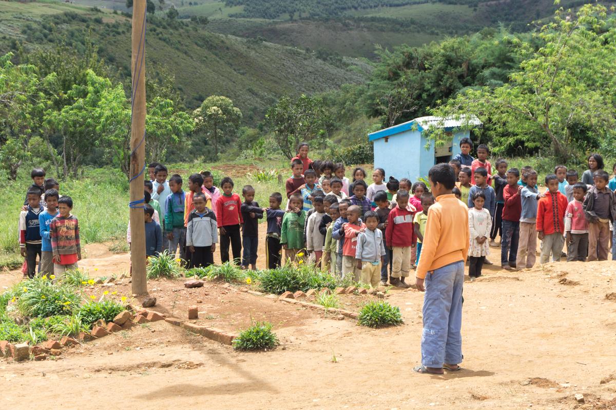 Foule d'enfants qui chantent l'hymne national de Madagascar devant l'école