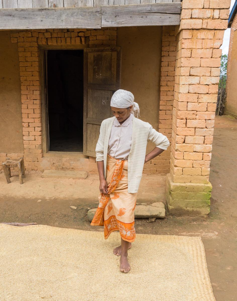 Dame malgache qui écrase des grains de riz à Anjozorobe, Madagascar