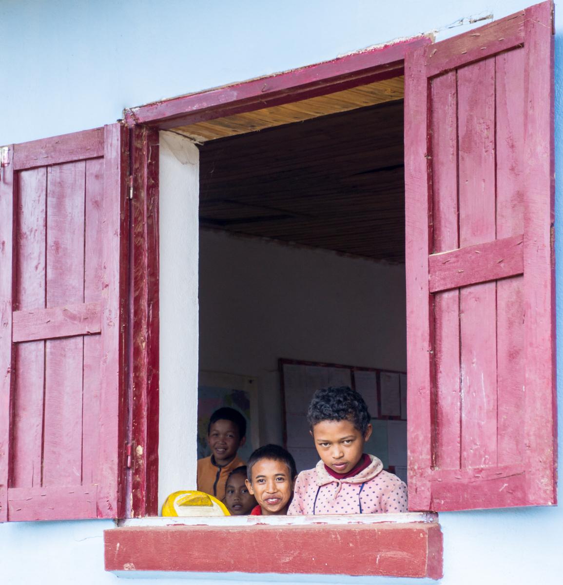 Enfants devant la fenêtre de l'école à Madagascar