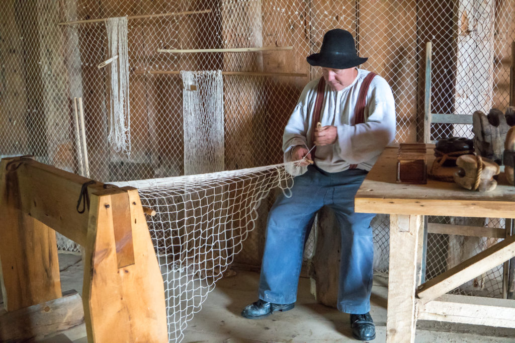 Artisan qui tresse des filets au Village Historique Acadien