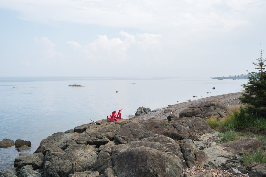 Le Camping au Rocher boisé - Chaises rouges devant la Baie des Chaleurs