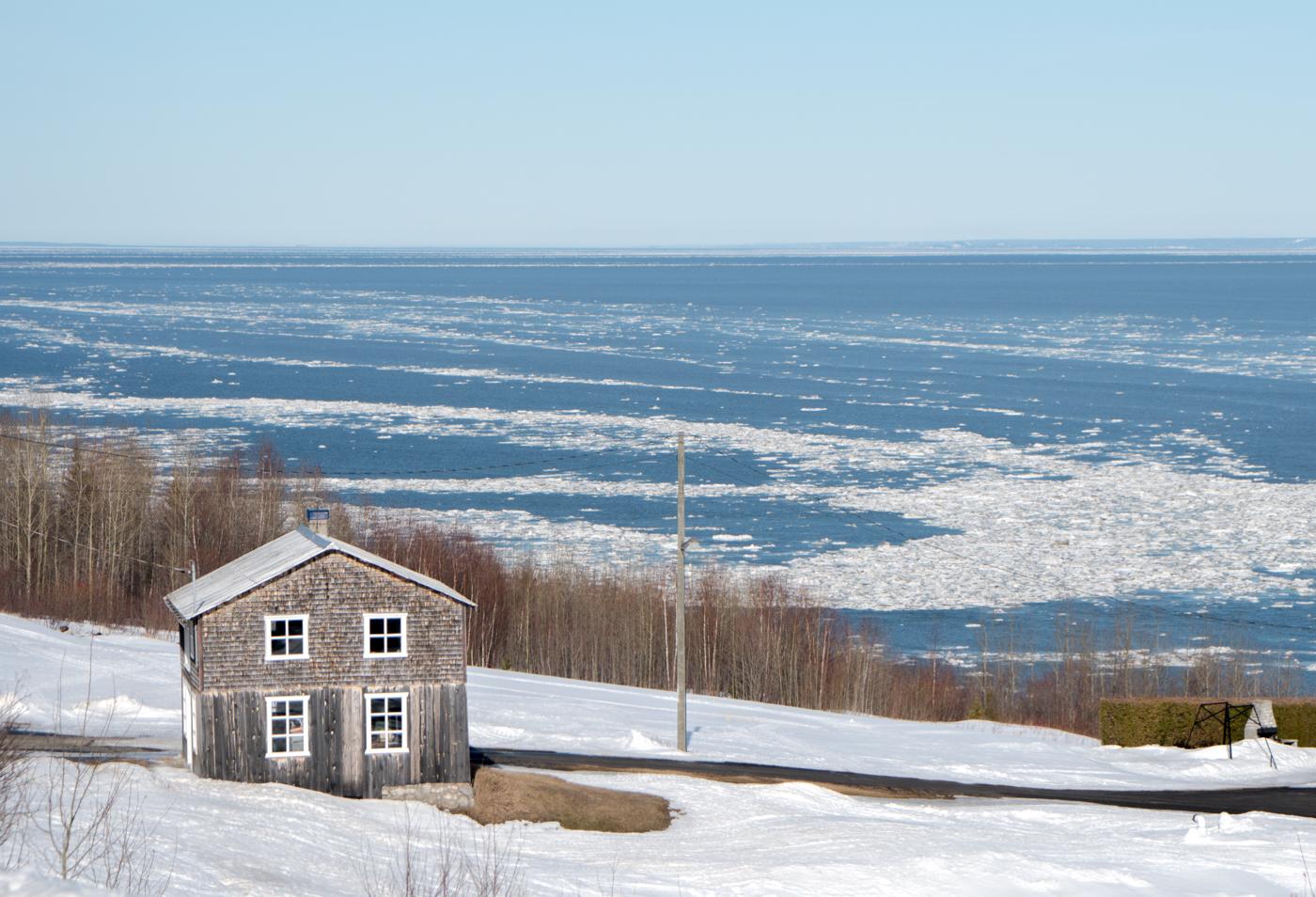 Petite maison blanche dans la neige de l'hiver de Charlevoix