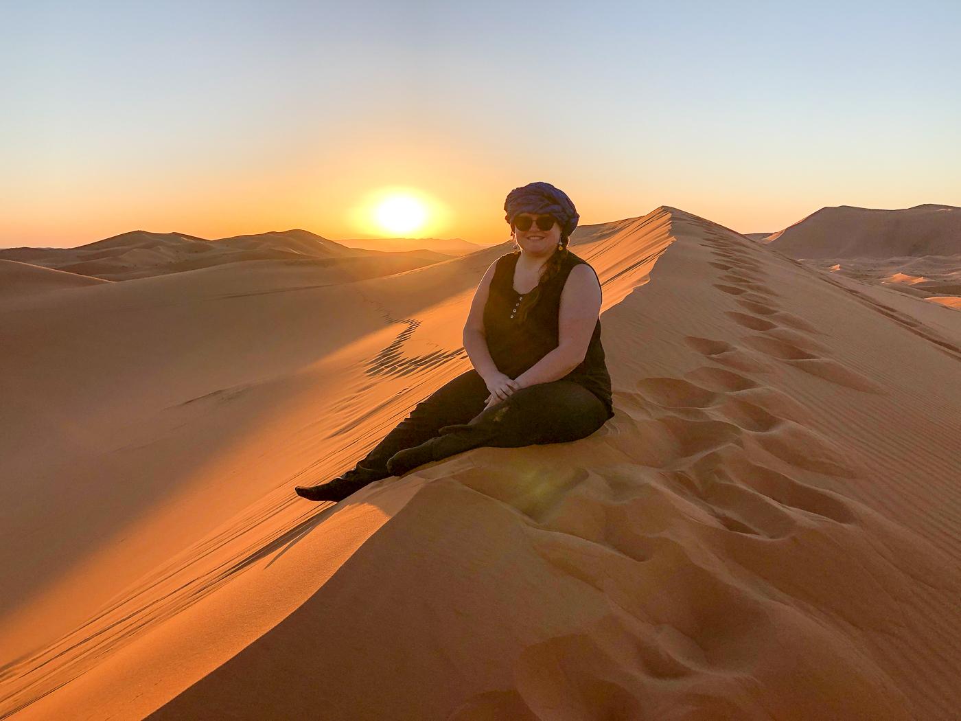 Jennifer assise sur une dune de sable dans le désert du Sahara près de Merzouga au Maroc
