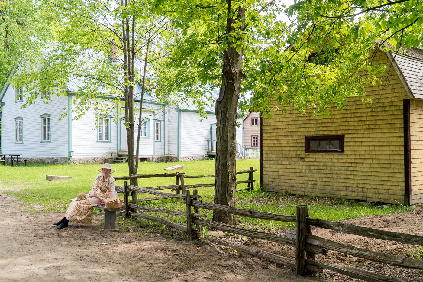 Personnage assis au Village québécois d'antan, un incontournable à faire à Drummondville