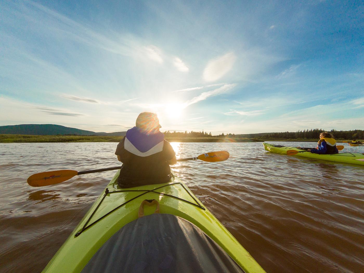 Kayak sur l'eau au coucher de soleil - Bucket list au Canada