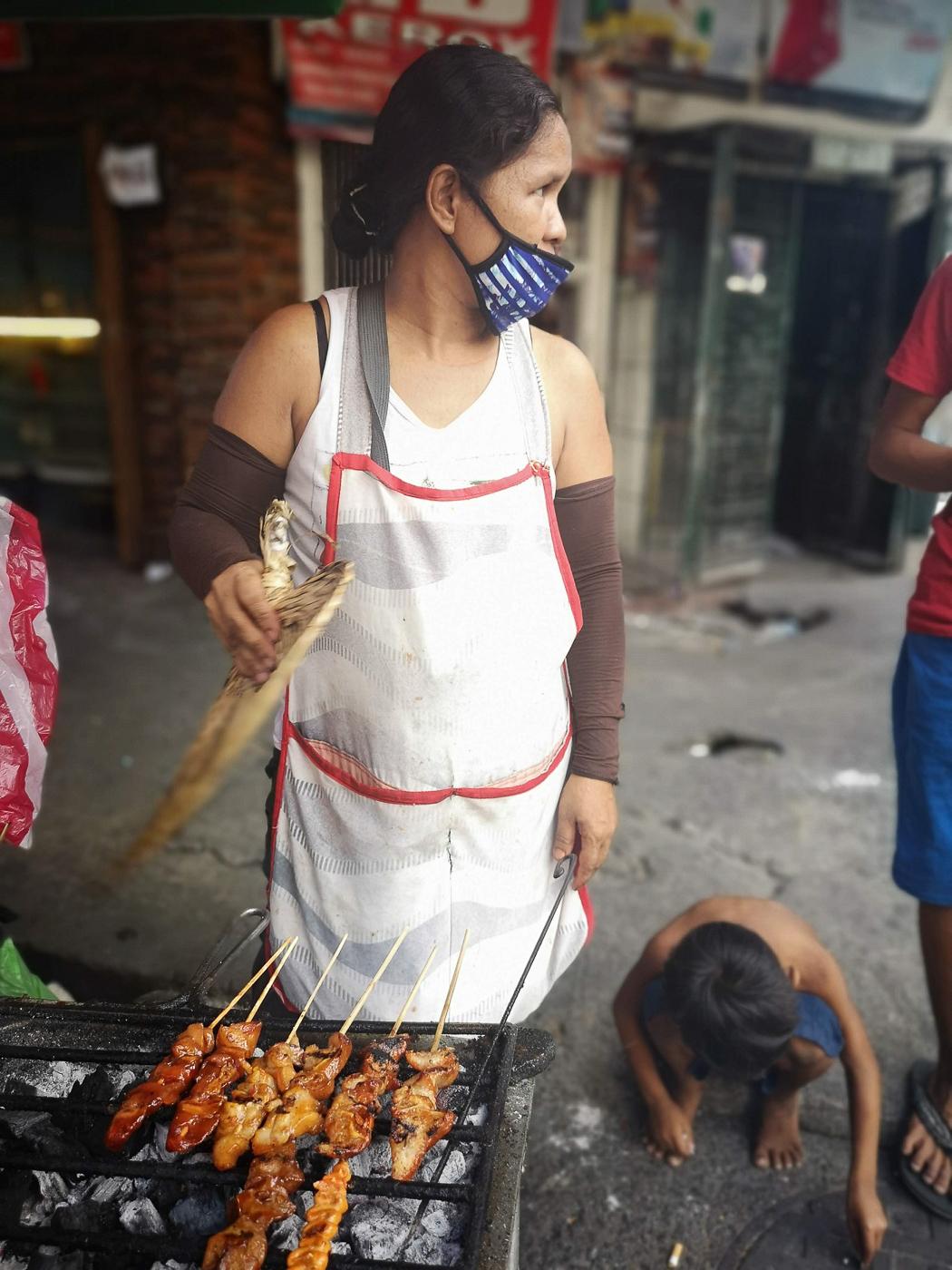 Femme grillant des brochettes philippines