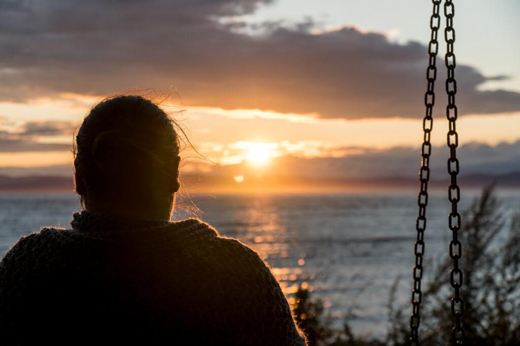 Anne assise sur un banc au coucher de soleil
